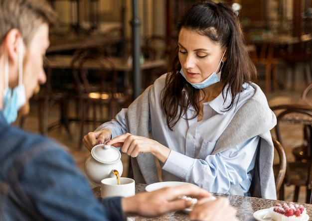 Mana e mulher bebendo chá com máscaras no queixo