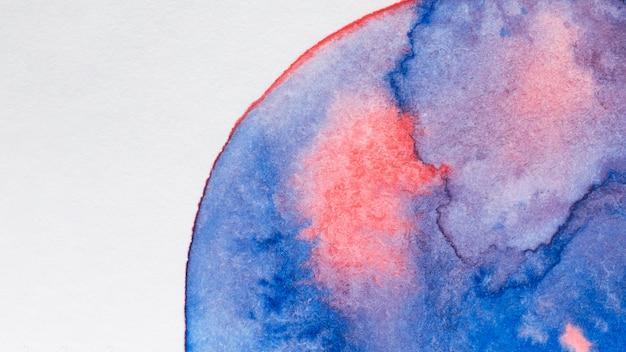 Mancha azul e rosa pintada à mão na superfície branca