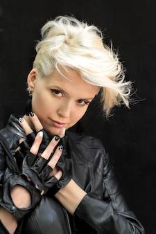 Mancha de cinza da moda e corte de cabelo no cabelo curto na modelo vestida com uma jaqueta de couro preta e luvas.
