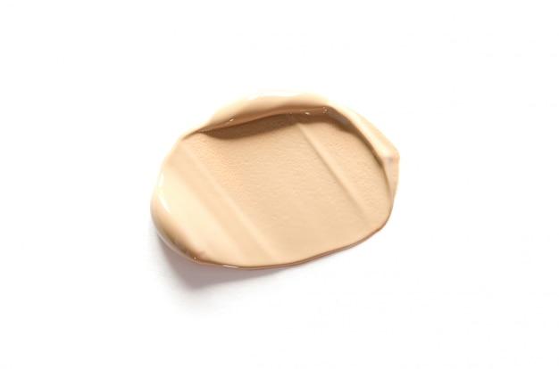Mancha de maquiagem bege de fundação cremosa isolada no branco