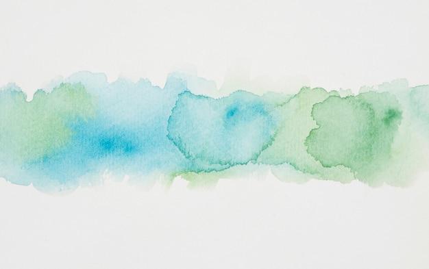 Manchas azuis e verdejantes de tintas em papel branco