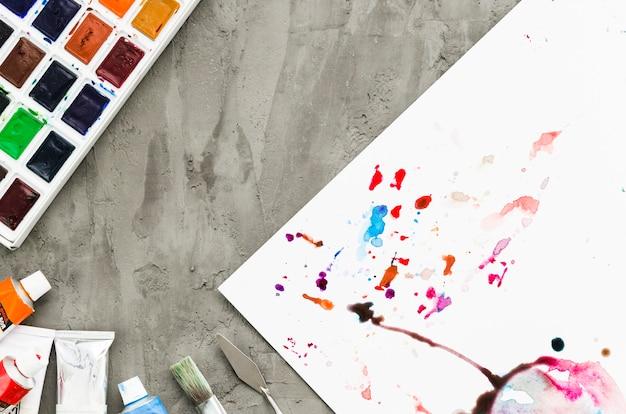 Manchas de aquarela vista superior no papel e aquarela paleta