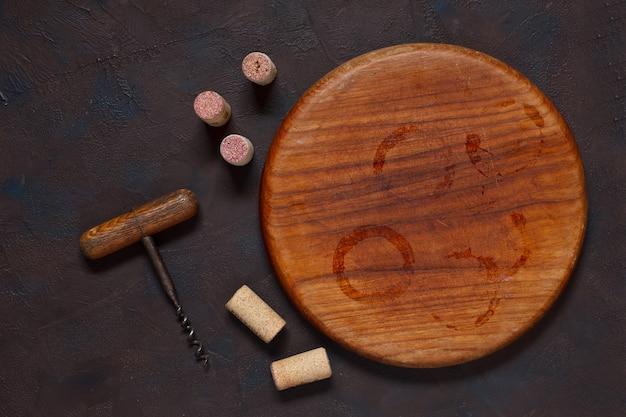 Manchas de vinho na placa de madeira redonda, rolhas e saca-rolhas.