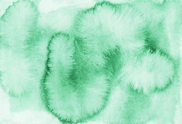 Manchas verdes de aquarela em fundo de papel branco. pintado à mão