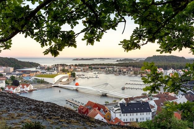 Mandal, uma pequena cidade no sul da noruega. visto de altura, com um penhasco e um carvalho em primeiro plano.