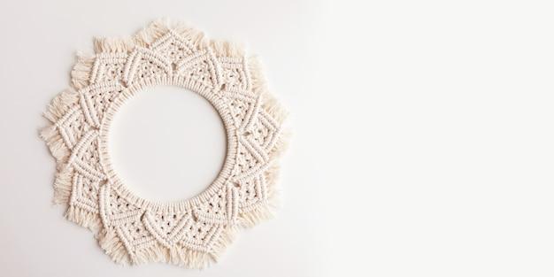 Mandala macramê. grinalda de macrame em uma superfície branca close-up. fio de algodão natural. eco decoração da casa. bandeira. copie o espaço