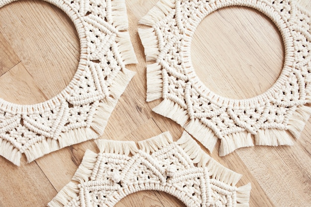 Mandalas macramé. flores de macramé em um fundo de madeira close-up. fio de algodão natural. eco decoração da casa. foco suave.