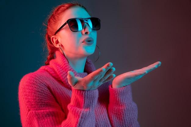 Mandando beijos. retrato da mulher caucasiana isolado no fundo do estúdio gradiente em luz de néon. linda modelo feminino com óculos escuros, cabelo vermelho. conceito de emoções humanas, expressão facial, anúncio.
