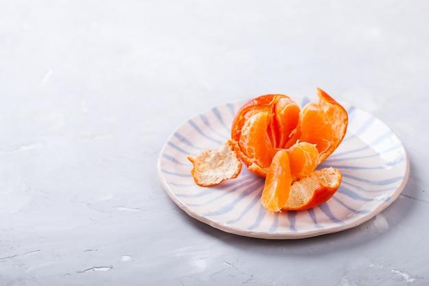 Mandarim em uma placa, em uma luz background.citrus. copie o espaço. conceito de saudável eating.selective focus.