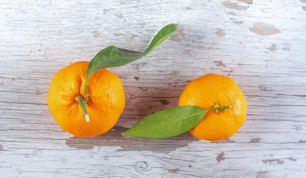 Mandarinas com folhas na superfície de madeira