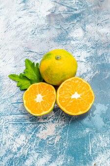 Mandarinas de corte de vista inferior em espaço livre de superfície branco azul