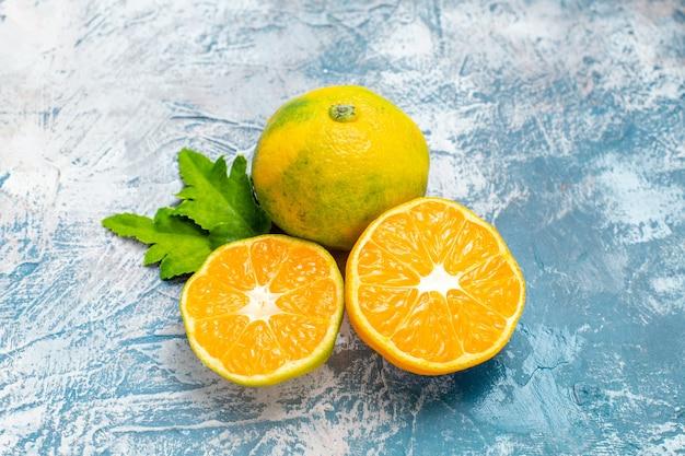 Mandarinas de corte de vista inferior na superfície azul e branca