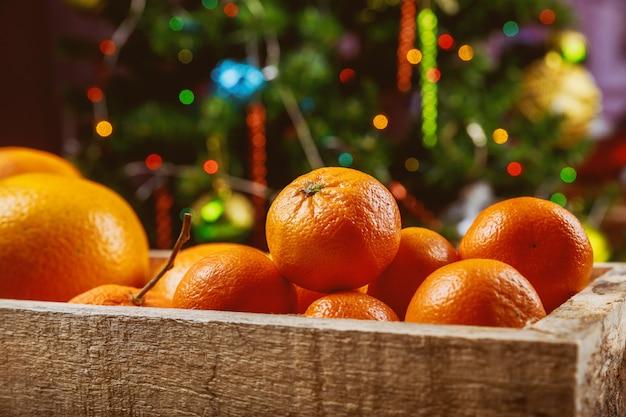 Mandarinas em caixa de madeira com árvore de natal.