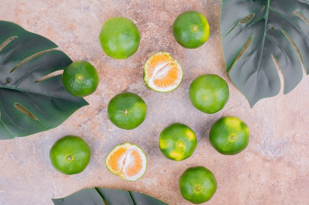 Mandarinas em uma superfície com folhas verdes