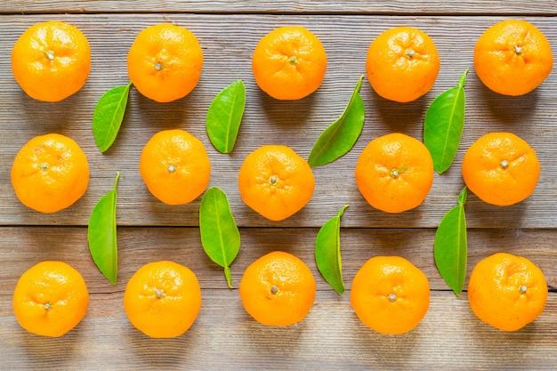 Mandarinas frescas com folhas na velha mesa de madeira