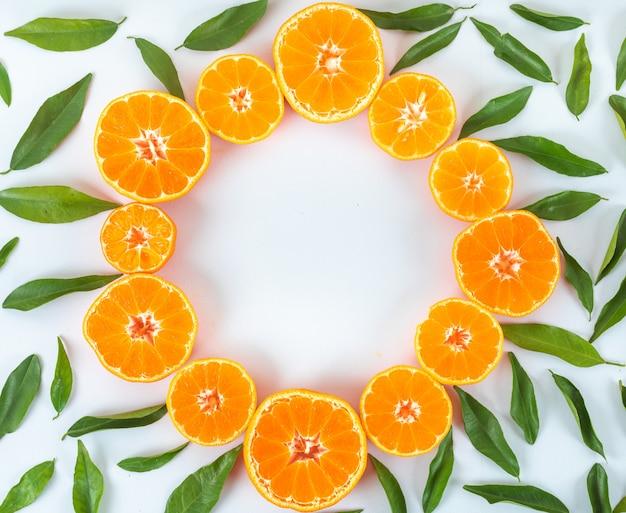 Mandarinas frescas de vista superior decoradas com folhas na superfície branca