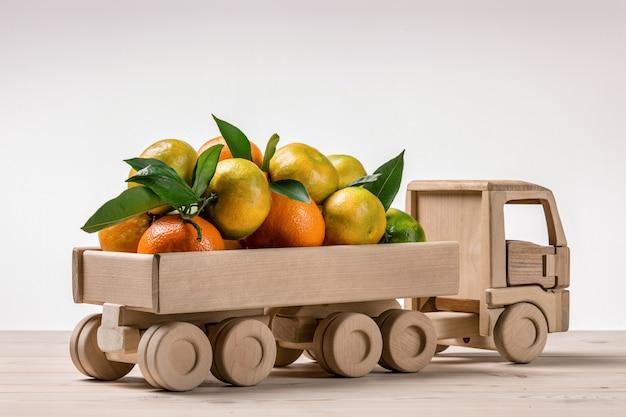 Mandarins na parte traseira do caminhão de brinquedo.