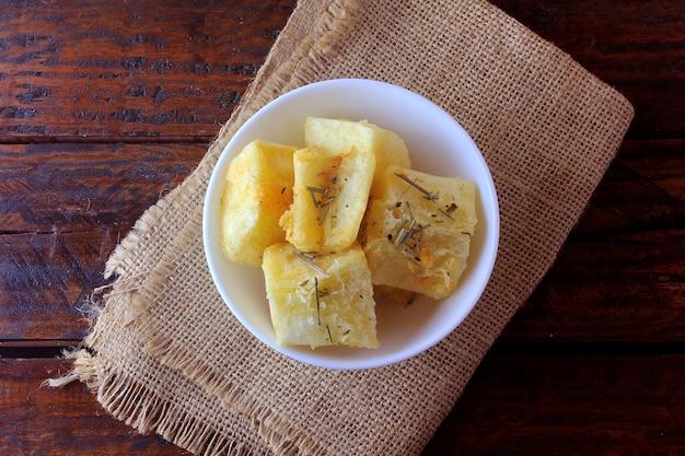 Mandioca cozida e frita (mandioca) na tigela de cerâmica na mesa de madeira rústica no restaurante