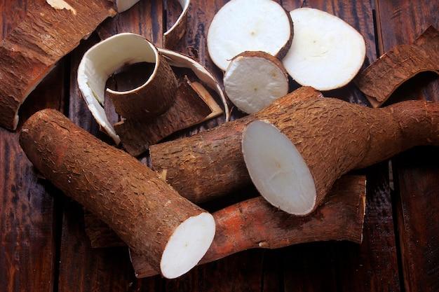 Mandioca fresca e cascas e fatias na mesa de madeira rústica