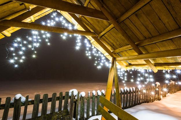 Mandril de madeira com luzes de natal fica em uma encosta de esqui no nevoeiro inverno da noite, num contexto de pinheiros nevados. conceito de relaxamento em uma estação de esqui