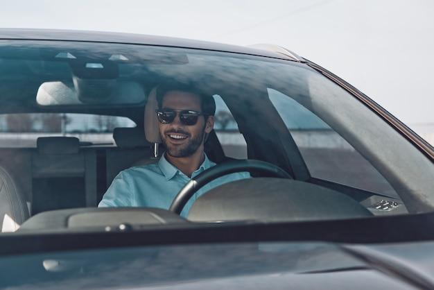 Maneira conveniente de viajar. jovem bonito sorrindo enquanto dirige um carro de status