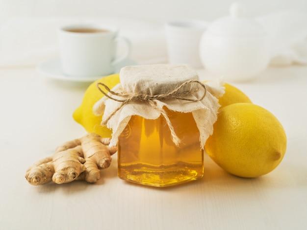 Maneiras populares para tratar um resfriado - um pote de mel, gengibre, limões no fundo branco, vista lateral