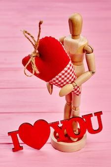 Manequim boneco de madeira apaixonado, segurando o coração.
