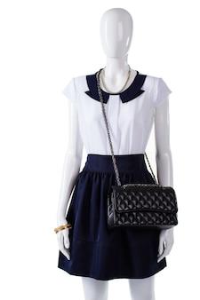 Manequim com bolsa acolchoada preta. bolsa acolchoada e saia azul marinho. bolsa feminina de couro acolchoado. nova bolsa acolchoada em exibição.