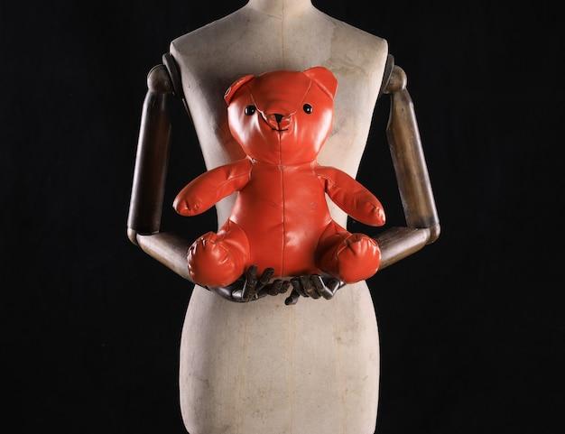 Manequim com um urso de brinquedo em um fundo preto