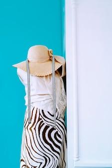 Manequim de design de moda com tecidos, fita métrica e chapéu. foto vertical