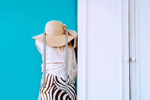 Manequim de design de moda com tecidos, fita métrica e chapéu. paredes azuis