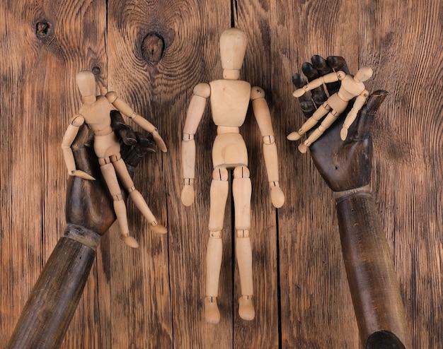Manequim de madeira nas mãos de um manequim