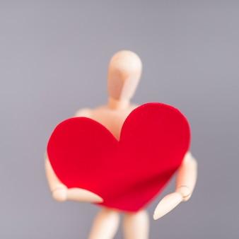 Manequim de madeira segurando coração vermelho grande