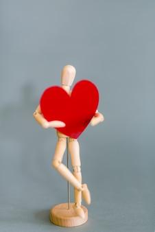 Manequim de madeira segurando coração vermelho