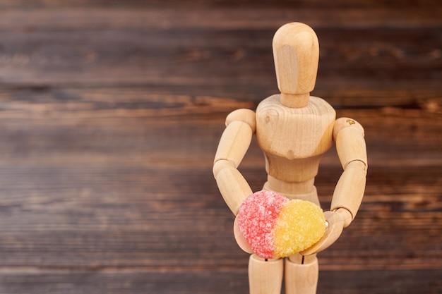 Manequim de madeira segurando doces açucarados. boneco de madeira com bala de geléia em forma de coração em fundo de madeira marrom e espaço de cópia.