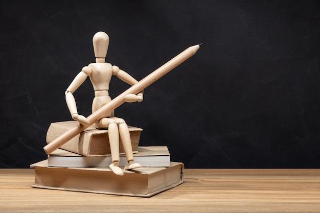 Manequim de madeira, segurando um lápis, sentado sobre uma pilha de livros. voltar para o fundo da escola