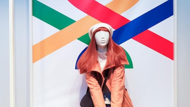 Manequim de uma mulher em luxuosas roupas de inverno ou outono em uma vitrine. um manequim feminino de cabelos vermelhos mostra uma coleção casual de roupas. casaco marrom.