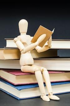 Manequim sentado em uma montanha de livros de leitura