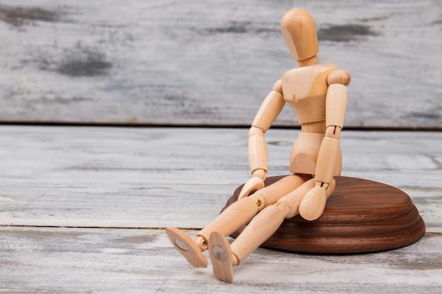 Manequim sentado na madeira.