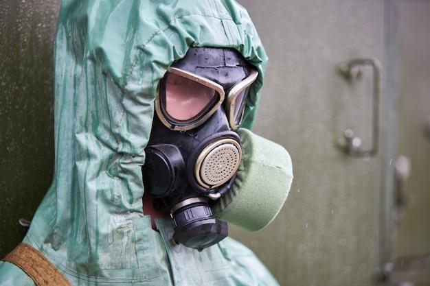 Manequim vestido com roupa de proteção química de borracha verde e máscara de gás preta, close-up
