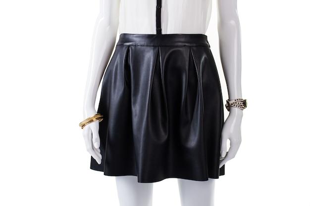 Manequim vestindo saia e acessórios. peça feminina de couro com relógio. saia elegante de cor escura. aparência elegante e atraente de menina.