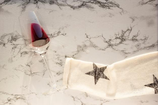 Manga da camisola segura o copo de vinho tinto na mesa de mármore