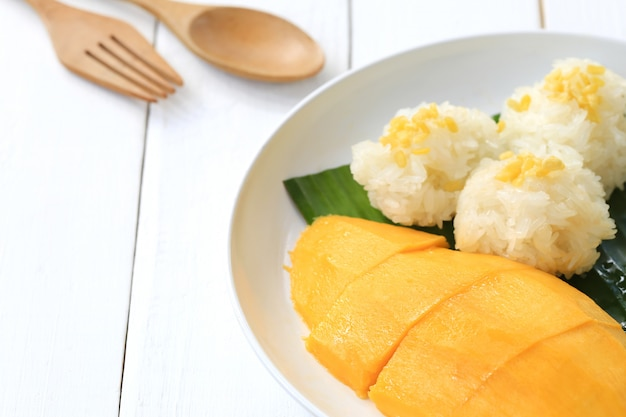 Manga e arroz pegajoso no prato branco no assoalho de madeira branco.