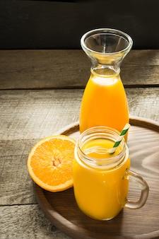 Manga e suco de laranja e fatia de laranja na tabela de madeira. bebida fresca e saudável.