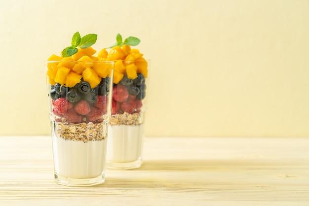 Manga, framboesa e mirtilo caseiros com iogurte e granola - estilo de comida saudável