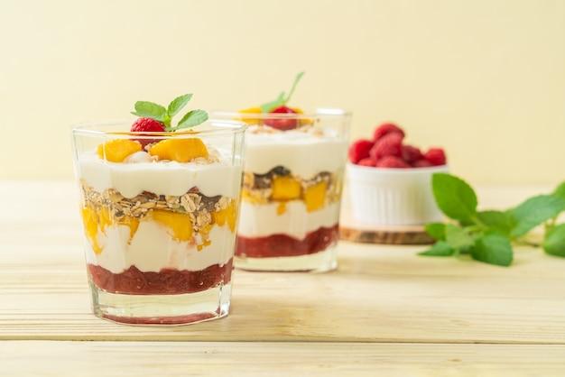 Manga fresca caseira e framboesa fresca com iogurte e granola - estilo de comida saudável