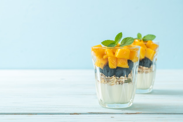 Manga fresca caseira e mirtilo fresco com iogurte e granola - estilo de comida saudável