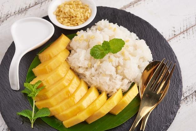 Manga madura e arroz com leite de coco na superfície da pedra, sobremesa doce tailandesa na temporada de verão.