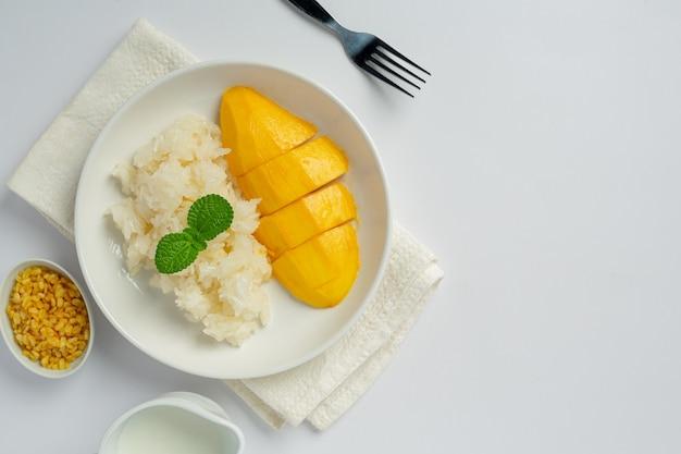 Manga madura fresca e arroz pegajoso com leite de coco na superfície branca