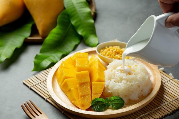 Manga madura fresca e arroz pegajoso com leite de coco na superfície escura